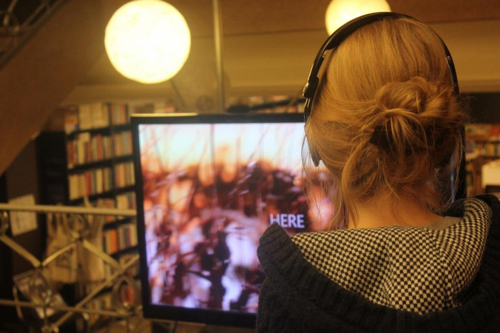 a woman watches a poetry video in a bookstore