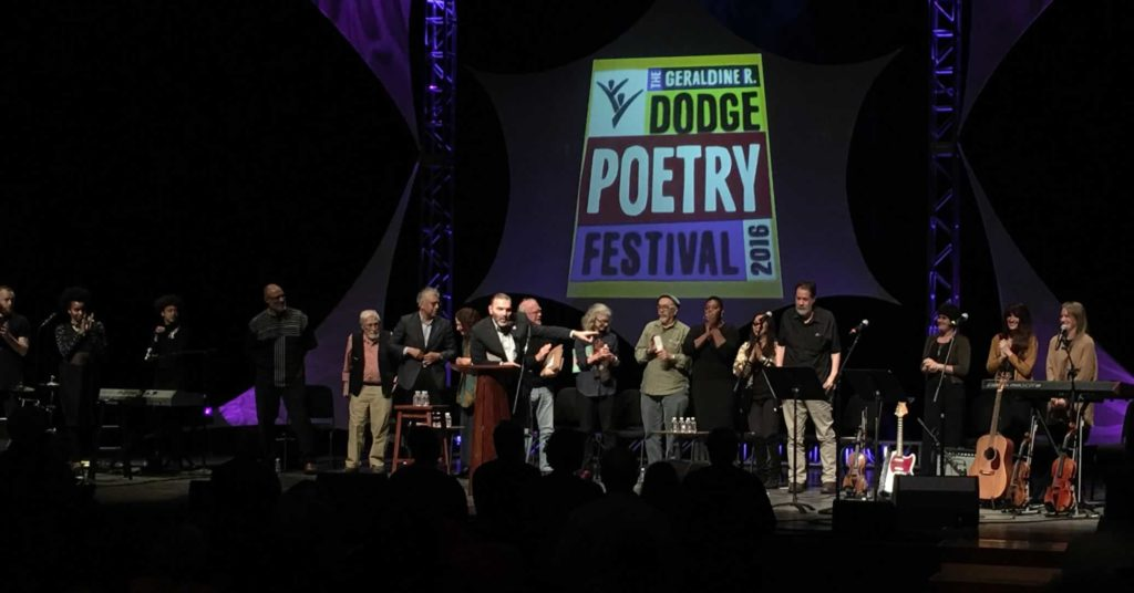 Martin Farewell, Director of the Dodge Poetry Program asks audience to give a hand to ten poets and two musical groups at Poetry like Bread: Poems of Social and Political Consciousness.