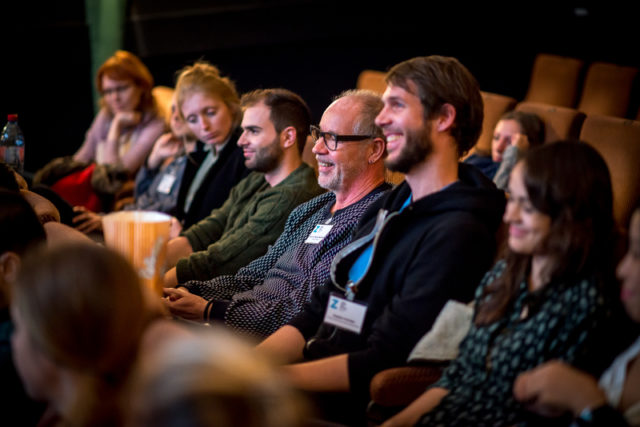 theater audience members seen from the side, smiling at the screen